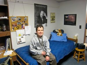 Micah sitting in his dorm room at Oakland University